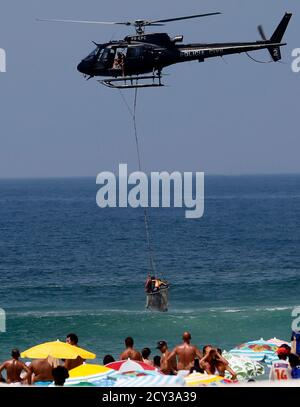 Rescue workers lift a drowning swimmer with a helicopter at Ipanema beach in Rio de Janeiro January 20, 2015.  REUTERS/Sergio Moraes (BRAZIL - Tags: SOCIETY TRANSPORT)