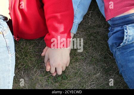 L'amore della madre nella mano, sul palmo. Madre che tiene una mano del suo figlio all'aperto. Foto Stock