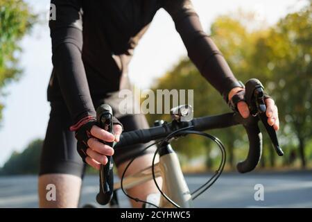 Mani di un ciclista poggiate sul manubrio della moto da strada. Ciclismo, allenamento di sport in bicicletta all'aperto Foto Stock