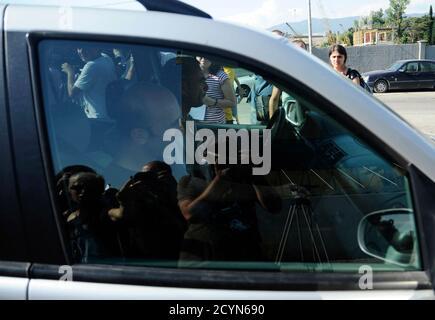 Due uomini, uno dei quali è presumibilmente ex fotografo presidenziale georgiano Irakli Gedenidze (di fronte), allontanano da un palazzo di corte a Tbilisi 22 luglio 2011. Venerdì i procuratori georgiani hanno chiesto a un tribunale di dare prova a quattro fotografi detenuti due settimane fa sospettando di spionare per la Russia, il che significa che potrebbero essere presto rilasciati. REUTERS/Nodar Tskhvirashvili (GEORGIA - Tags: LEGGE SUL CRIMINE POLITICA DEI MEDIA)