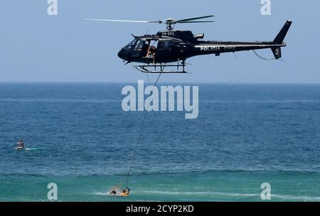 Rescue workers prepare to lift a drowning swimmer with a helicopter at Ipanema beach in Rio de Janeiro January 20, 2015.  REUTERS/Sergio Moraes (BRAZIL - Tags: SOCIETY TRANSPORT)