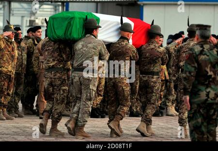 Italian soldiers carry the coffin of an Italian soldier killed in Herat province March 1, 2011. An Italian soldier was killed and four wounded by a roadside bomb near Shindand in western Herat province on Monday, the Italian Defence Ministry said. The ISAF confirmed one of its troops was killed in the area but gave no further details. REUTERS/Mohammad Shoib (AFGHANISTAN - Tags: MILITARY OBITUARY)