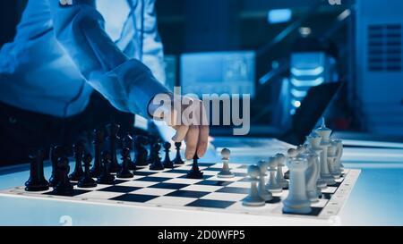 Primo piano colpo di intelligenza artificiale che aziona un braccio robotico futuristico in un gioco di scacchi contro un uomo. Robot sposta un'alba. Sono in un