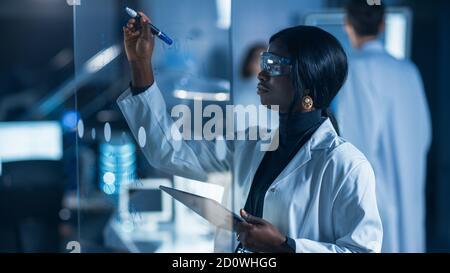 Nel laboratorio di Ricerca intelligente e bella African American femmina Lo scienziato che indossa il camice bianco e gli occhiali protettivi scrive la formula sopra Vetro