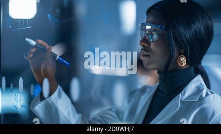 Primo piano di una bella e intelligente African American Female Lo scienziato che indossa il camice bianco e gli occhiali protettivi scrive la formula sopra Lavagna bianca in vetro