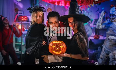 Festa del costume di Halloween: Il conte del padre Dracula tiene la figlia piccola della ragazza della bat e gli hugs moglie della strega per un ritratto felice della famiglia. In background Foto Stock
