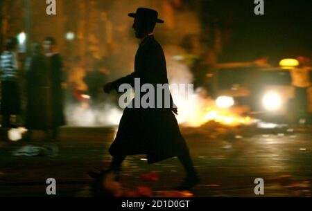An Ultra-Orthodox Jewish man walks past burning tires during a protest against an up-coming Gay Parade in Jerusalem November 1, 2006.   REUTERS/Ronen Zvulun (JERUSALEM)