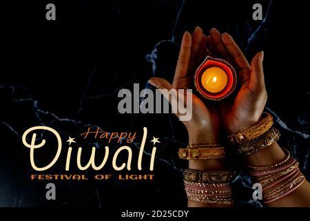 Happy Diwali - Donna mani con hennè che tiene accesa candela isolato su sfondo scuro. Lampade Clay Diya illuminate durante Dipavali, festa indù delle luci ce Foto Stock