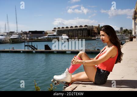 Vista laterale giovane femmina pattinaggio a rotelle lungo la banchina in legno città d'estate