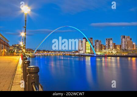 Una vista che guarda lungo il fiume Tyne al tramonto dalla banchina di Newcastle verso il Gateshead Millennium Bridge, il Baltic Arts Center e Gateshead Quays.