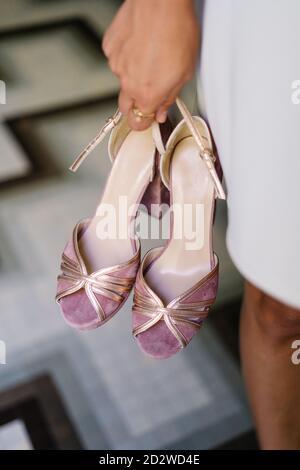Alto angolo di raccolto anonimo femmina in piedi con coppia di scarpe eleganti con tacco alto su sfondo sfocato del pavimento negozio