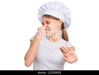 Ragazza che indossa un cappello dello chef, pizzica il naso con le dita guarda con disgusto, isolato su sfondo bianco. Foto Stock