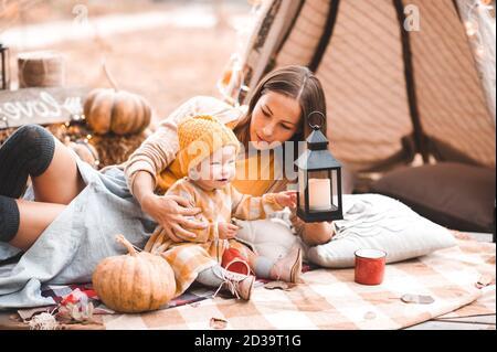 Madre che tiene ragazzina 1-2 anni che posa all'aperto con decorazione stagione autunno primo piano. Maternità. Foto Stock