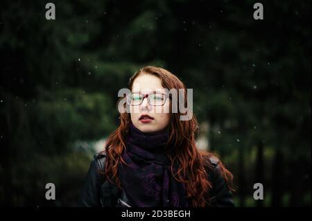 Bella ragazza giovane con capelli rossi su sfondo verde naturale. I fiocchi di neve stanno cadendo intorno. Capelli rossi, verniciati con hennè. Foto Stock