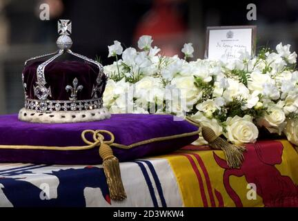 The ceremonial crown of the Queen Mother lies on top of her flag-draped coffin next to a wreath from Queen Elizabeth II during the ceremonial procession in central London, April 5, 2002. [Thousands of mourners lined the route to pay their last respects to the Queen Mother who died last aged 101. The funeral will take place on April 9 after which she will be interred at St George's Chapel in Windsor next to her late husband King George VI.]