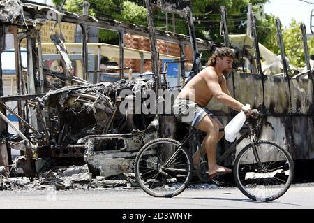 Un uomo guida la sua bicicletta vicino a un autobus bruciato a Grota slum a Rio de Janeiro, 25 febbraio 2003. La capitale brasiliana del Carnevale di Rio ha vissuto un'altra notte di disordini mentre le bande di droga hanno tormentato gli autobus e attaccato i negozi. Il festival del Carnevale inizia il 1 marzo. REUTERS/Sergio Moraes SM Foto Stock