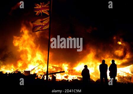 Northern Irish stand in front of a bonfire in the Protestant heartland Shankill Road area of central Belfast at the height of the Protestant marching season early July 12, 2002. Pro-British protestants set traditional bonfires to commemorate William of Orange's victory over King James at the Battle of the Boyne on July 12, 1690.