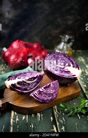 Primo piano affettato e mezzo di cavolo viola sopra sfondo rustico Foto Stock