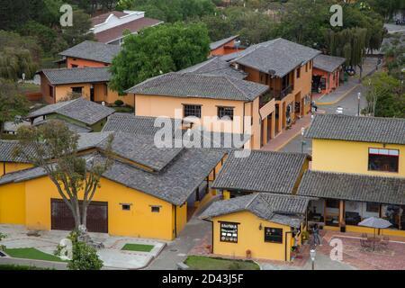 villaggio con diverse piccole case gialle e rosa con tetto di tegole nere, alberi tra le case Foto Stock