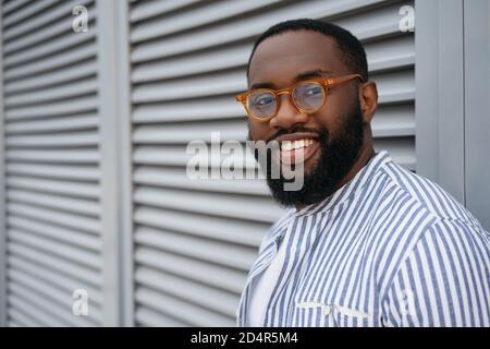 Primo piano ritratto di un uomo afro-americano di successo che indossa occhiali eleganti. Bel modello guardando la fotocamera, sorridente, isolato sullo sfondo