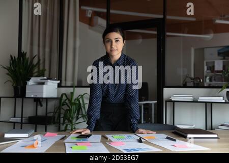 Ritratto di giovane donna d'affari indiana fiduciosa che posa in carica Foto Stock