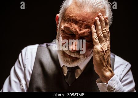 Ritratto di uomo anziano depresso su sfondo nero. Foto Stock