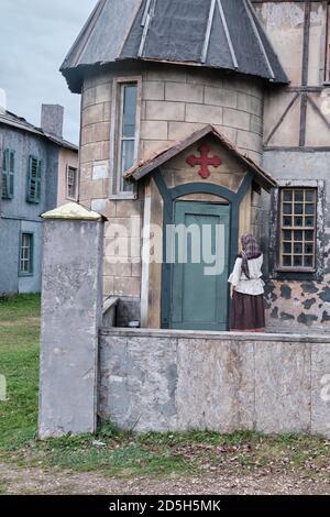 Una donna in un vecchio vestito nel cortile di Una vecchia Chiesa cattolica con una grande croce rossa la porta