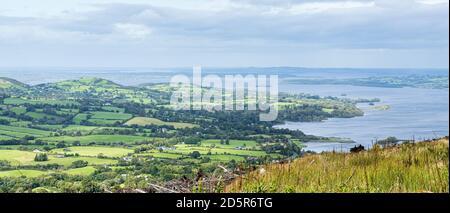 Campi verdi e campagna rurale che si affacciano su Lough Derg a Ballycunggarran, County Clare, Irlanda
