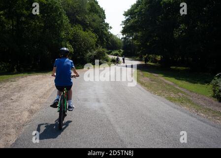 Un ragazzo adolescente segue la sua famiglia ma si tende indietro Una strada di campagna nel New Forest Hampshire Inghilterra ON un giro in bicicletta per tutta la famiglia
