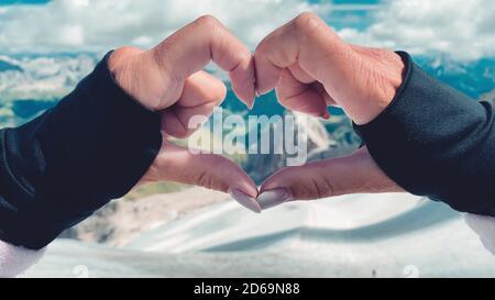 Donna che crea il segno del cuore con le mani su uno scenario di montagna. Foto Stock