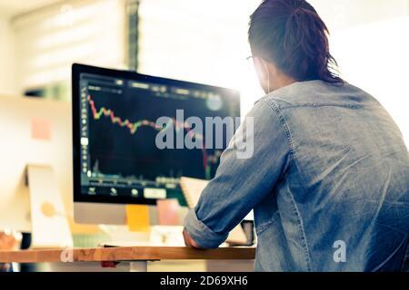 Vista posteriore di un uomo d'affari asiatico lavoratore d'ufficio indossare maschera lavorare con l'analisi di grafico in un nuovo ufficio normale con social tabella delle distanze da evitare