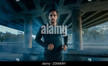 Ritratto Tiro di un giovane atletico muscoloso in Sport vestito jogging in strada. Sta funzionando in un ambiente urbano sotto un ponte. Foto Stock