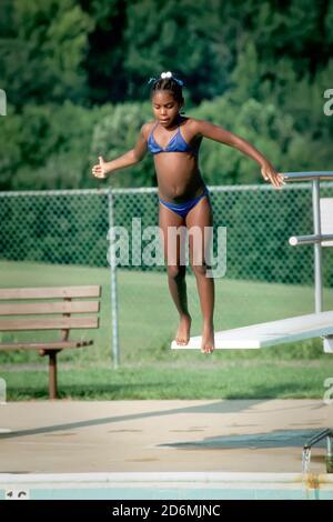 Una giovane femmina nero salta fuori da un trampolino in una piscina pubblica