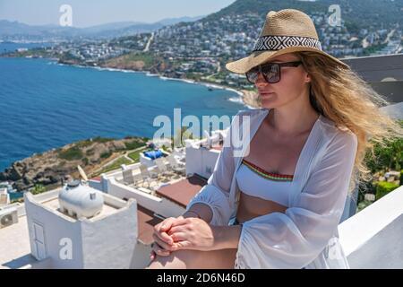 Bella giovane donna in abito bianco cappello di paglia sulla terrazza bianca balcone di casa o hotel con vista mare