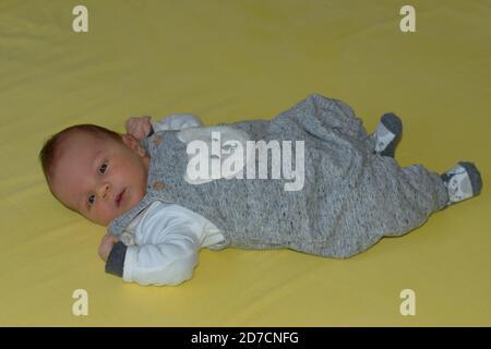 Closeup del bambino neonato carino sdraiato su sfondo giallo Foto Stock