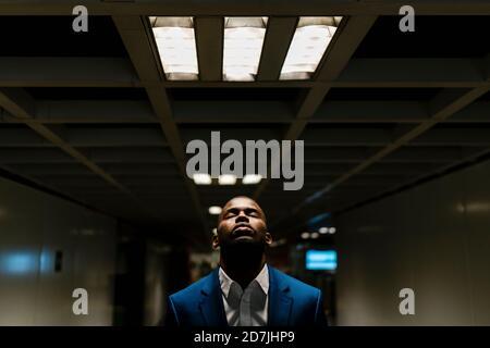 Maschio professionale con occhi chiusi in piedi sotto luce illuminata in metropolitana