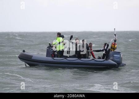 RITRASMISSIONE della distanza di modifica ottenuta in salto a 40 m. L'ex paracadutista John Bream (centro, braccio sollevato) è raccolto dall'acqua dopo il suo tentativo di record per il salto più alto senza un paracadute saltando 40 m da un elicottero nel mare al largo di Hayling Island in Hampshire.