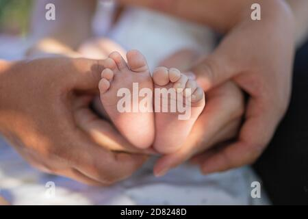 La bambina si piedi nelle mani dei genitori. Fascio solare. Esterno. Primo piano Foto Stock