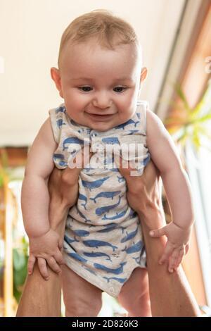 Fuoco selettivo delle mani del giovane padre che tengono il bambino sorridente bambino in aria e giocando mentre si sdraia sul divano a. casa