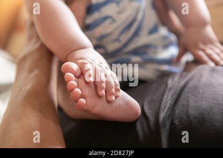 Messa a fuoco selettiva delle mani che toccano le gambe e i piedi del bambino ragazzo mentre riposava e sedeva sul ventre di suo padre con supporto a casa