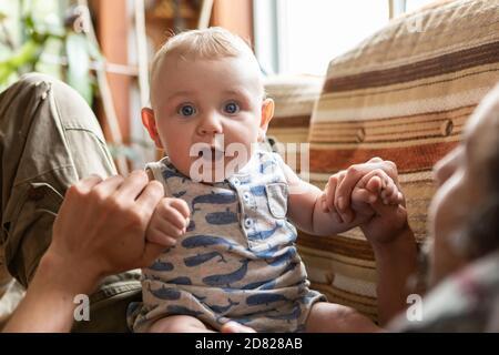 Ritratto di bambino allegro ed eccitato seduto sul padre sdraiato sul divano e tenendo le mani mentre si gioca e si salta sullo stomaco