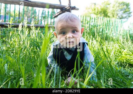 Ritratto del bambino infante di espressione pauroso che indossa i vestiti formali con prua seduta e sdraiata su erba sullo stomaco dentro parco all'aperto