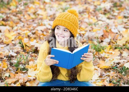 La conoscenza è seme che cresce quando si legge. Felice capretto ha letto il libro che siede sulle foglie di autunno. Giorno della conoscenza. 1 settembre. Istruzione primaria. Biblioteca scolastica. Pagina per pagina non è necessario attendere. Foto Stock