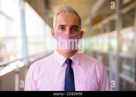 Faccia di uomo d'affari persiano con maschera al ponte pedonale dentro la città