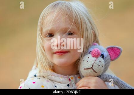 Primo piano ritratto della bella bambina bionda che abbraccia il suo giocattolo fatto a mano preferito (gatto lavorato a maglia) all'aperto. Giorno ventoso, capelli disordinati sul viso. Foto Stock