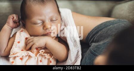 Vista superiore di una bambina che dormiva da lei trattenuta madre sulle mani Foto Stock