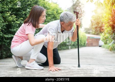 L'uomo anziano asiatico che cade a casa nel cortile causato da miastenia (debolezza muscolare) e l'infermiere è venuto per aiutare a sostenere. Concetto di vecchio sambuco