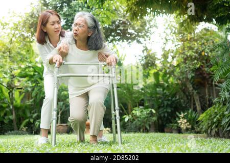 Donna anziana asiatica che cade a casa nel cortile causato da miastenia (debolezza muscolare) e la figlia è venuto per aiutare il sostegno. Concetto di vecchio e