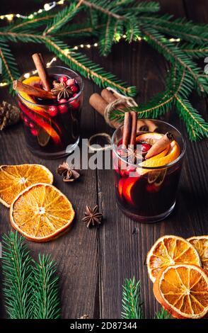 VIN brulé natalizio con mirtilli rossi, arancio e spezie su rustico fondo di legno. Bevanda calda invernale tradizionale.
