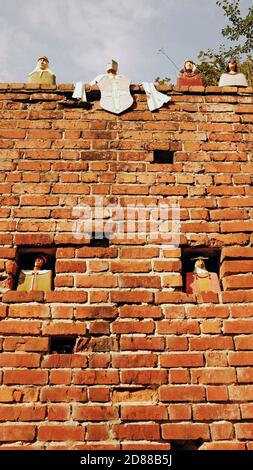 Busti in ceramica di scoppi medievali si trovano in cima, e nelle finestre, di un muro di mattoni nella città vecchia di Torun, Polonia. Foto Stock